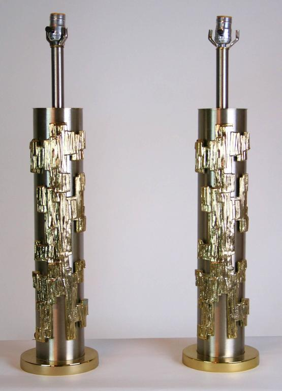 Chic pair of stainless steel cylinder lamps with applied abstract brass decoration, measures Shaft 4