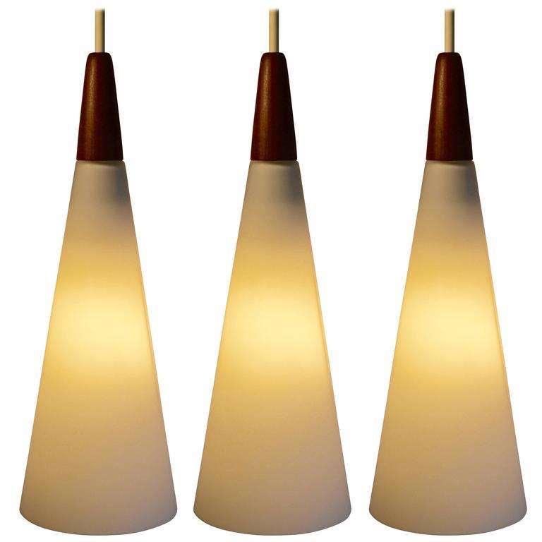 Set Of Three White Satin Glass And Teak Pendant Lights