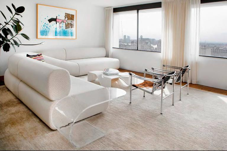 """This extended c-shaped side table with cantilevering top is made of 5/8"""" transparent recycled acrylic. Its top surface, at sofa height, seems to cantilever out, as if it were held down by screws. Because the lucite table's organic curved form is"""