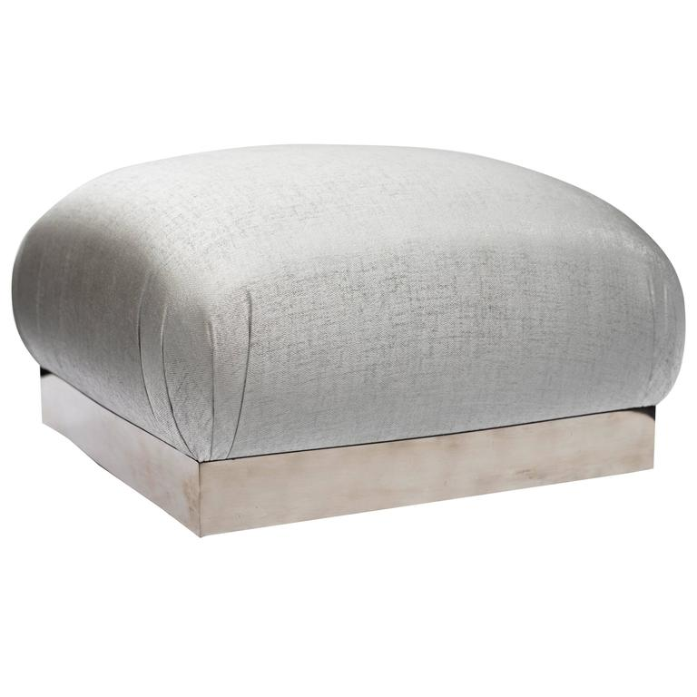 Elegant mid-century modern ottoman with iconic soufflé design and oversized features. Pouf has large square cushion with rounded edges and chrome banded base fitted with swivel casters. Newly upholstered in woven platinum mist (silver tones with sea