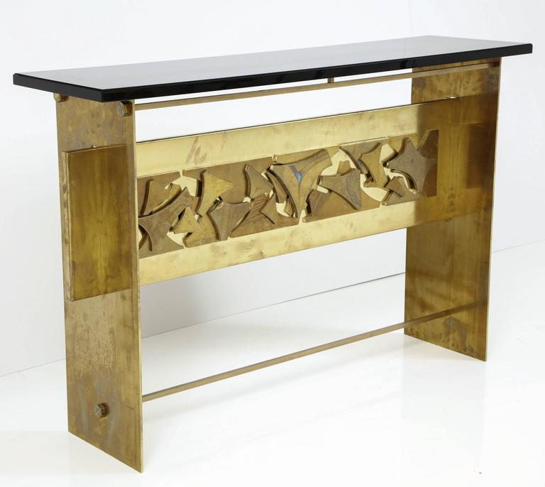 Elegant and edgy! This Italian Mid-Century style console is handmade of unlacquered brass with a one-of-a-kind sculptural relief in central panel. Finished with a sleek charcoal gray or black smoked Lucite top. Handmade in Italy. Pair available. On