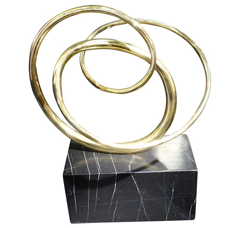 Contemporary German three bronze interlocking rings on black marble stand sculpture.
