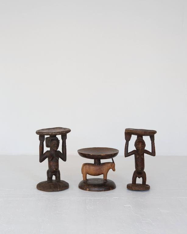 Unique solid wood African tribal stools with two figures of same relative size and a small goat stool. Estimated early 20th century. Available individually or as a set.