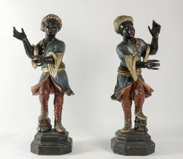 Lovely, gorgeous and rare pair of Venetian Nubian torcheres in hand-carved painted and gilded wood. Our Nubiens rests on original faux marble paint circular pedestal.  Early 19th century beautiful and decorative Italian, circa 1800.  Size: