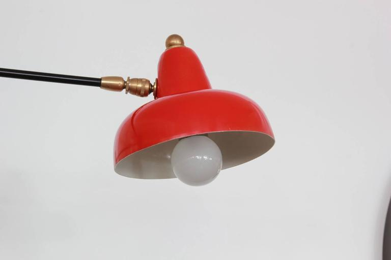 Italian counterbalance articulating wall sconce with original red metal shade, brass arm and hardware. Newly rewired.