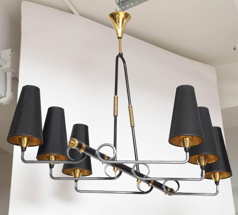 Very unusual and impressive asymmetrical linear six arm chandelier from France, circa 1950's, made of blackened iron with extensive brass embellishments and original brass trumpet horn ceiling canopy.  Stylized looping and curvilinear iron work
