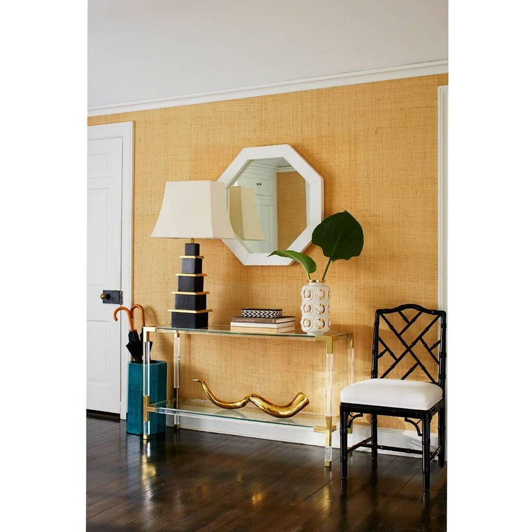 Clearly cool. The Jacques console is the perfect blend of simplicity and glamour, modern and traditional. Crafted with crystal clear acrylic and brushed brass corners. Fitted with a low glass shelf for baubles or books, the Jacques Console works