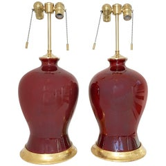 Pair of Sang De Bouef Oxblood Red Ceramic Lamps with Giltwood Bases