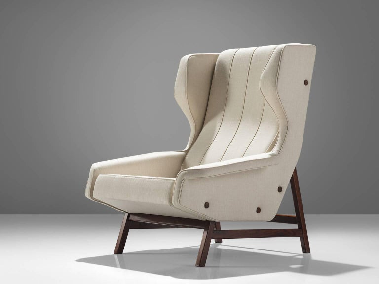 Gianfranco Frattini for Cassina, lounge chair model 877, fabric, rosewood, Italy, 1959.  Sturdy and voluminous lounge chair in white fabric, reupholstered in our in-house workshop. This wingback chair shows nice details and elegant lines. The