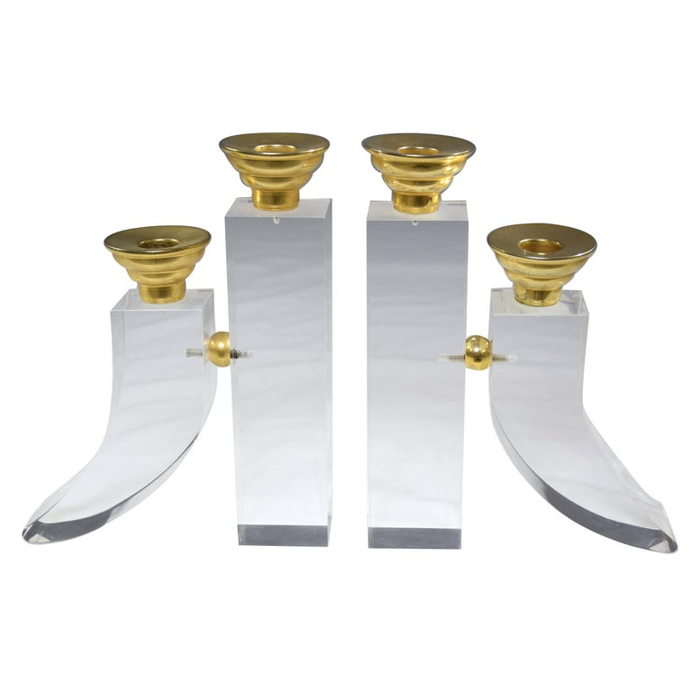 Pair of French 20th century vintage candleholders or candelabra each containing two candlestick holders set in curved block Plexiglas designs with polished brass details. The symmetrical styles are perfect for adding decorative allure to any living