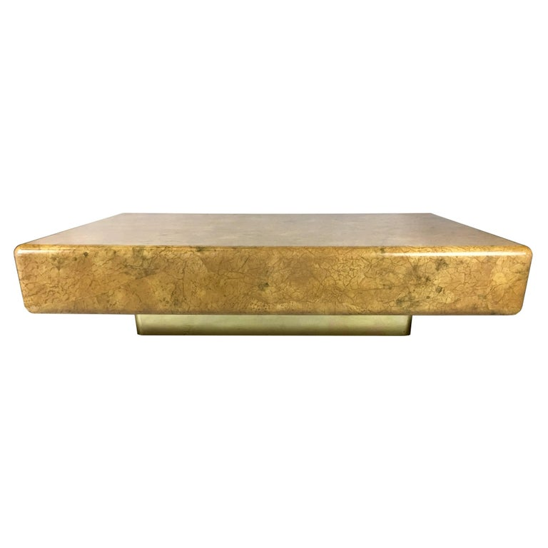 Large scale lacquered parchment coffee table raised on a brass clad recessed base in the style of Karl Springer. Top quality materials and workmanship.