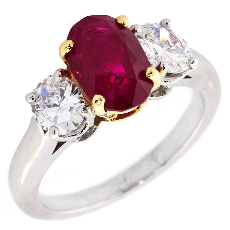 A classic platinum and 18k gold three-stone ring with a rare center Burma no-heat oval shape ruby weighing 2.64 ct, set between two diamond ovals weighing approx. 1.00 carat total.  Ruby specs (Based on accompanying American Gemological Laboratories