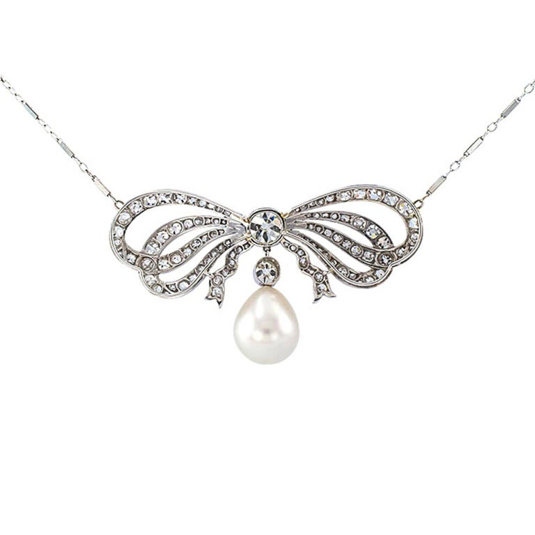 Edwardian Diamond and South Sea Pearl Bow Necklace  Centering upon a nice old Mine Cushion cut diamond weighing approximately 1.00 carat, approximately I - J color and VS clarity, tied up with a voluminous platinum bow, set with approximately 3.10