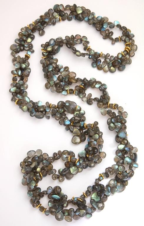 A necklace composed of labradorite beads and 18kt yellow gold rondelles. The individual bead and rondelle links are strung on cable wire, then woven together to form a chain. The flashes of color from  the labradorite range from blue to green to