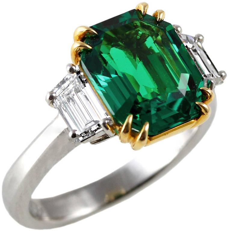 An exceptional three carat emerald-cut Muzo Colombian Emerald, set with two trapezoid diamonds with an estimated color-clarity of F-VS. The emerald exhibits superior color and clarity along with a certificate from AGL stating the origin as Classic