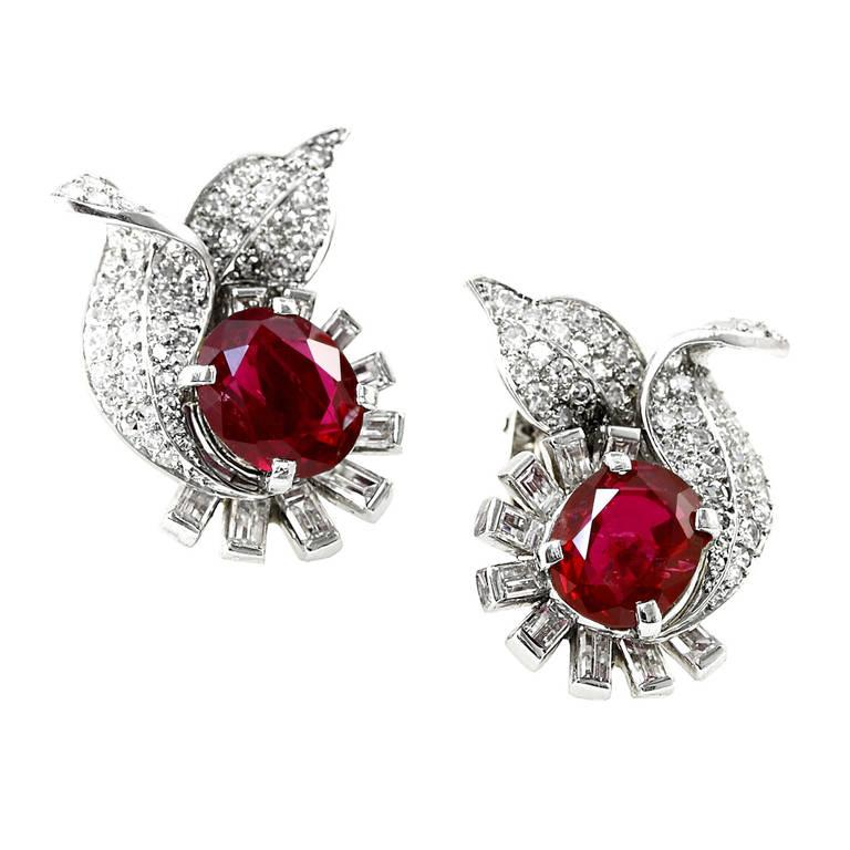 An exceptional pair of no heat burmese ruby earrings, each weighing over three carats, accented aesthetically with diamond baguette and old european cut diamonds. The earrings accompany a gemological certificate from AGL stating its origin as Burma,