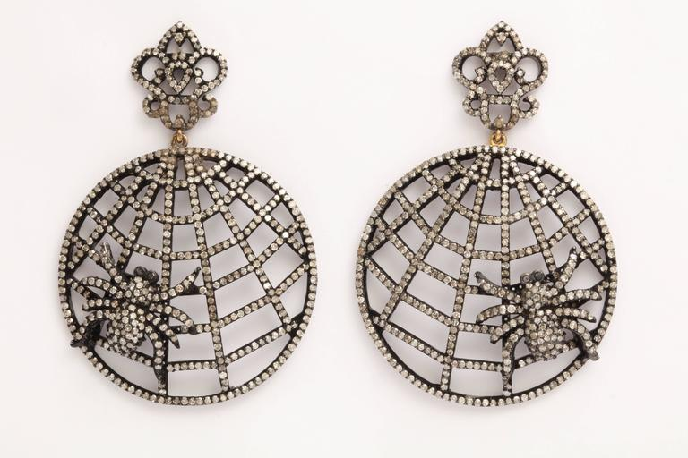 A pair of rhodium plated sterling silver and diamond spider web earrings. The webs are suspended from rhodium plated sterling silver and diamonds crowns. There are approximately 5.45cts of diamonds. Length: 2.20 inches Width: 1.50 inches Spider