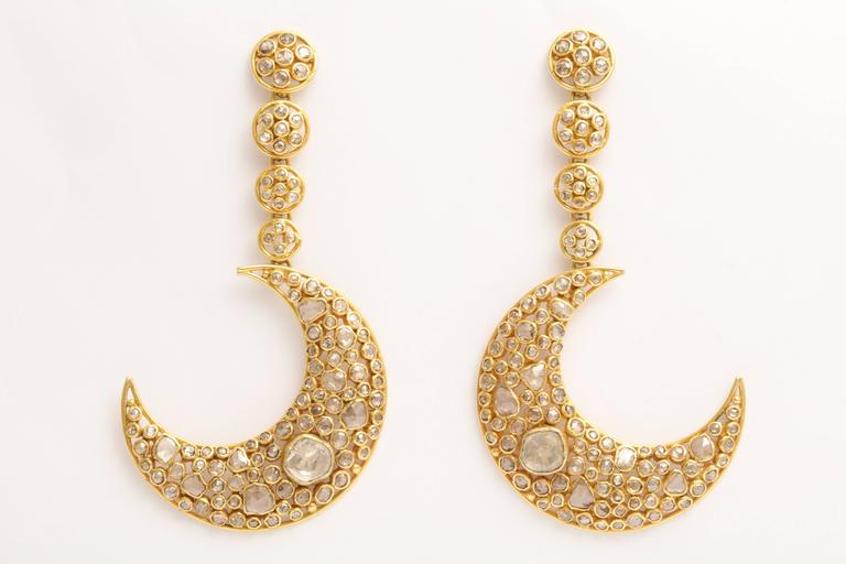 A pair of 18kt yellow gold and diamond moon earrings. The moons are suspended from graduated 18kt yellow gold and diamond set discs. The moons and discs are filled with bezel set rose cut diamonds and polki diamonds. The approximate diamond weight