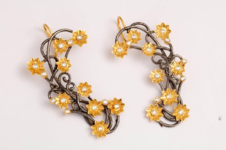 A par of ear cuffs composed of rhodium plated sterling silver vines, 18kt yellow gold flowers and rose cut diamonds.There are 1.68 cts of diamonds.  Length: 3.00 inches Width: 1.15 inches