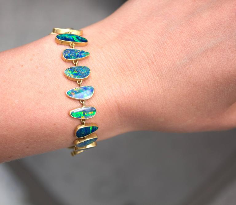 One of a Kind Bracelet handcrafted by acclaimed jewelry designer Kothari in matte-finished 18k yellow gold showcasing 21 beautifully-matched yet individually distinctive boulder opal gemstones featuring vibrant and electrifying play-of-color, all