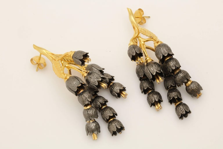 A pair of earrings composed of 18kt yellow gold leaves and rhodium plated sterling silver lily of the valley flowers which cascade down and 18kt yellow gold vine. Each flower has 18kt yellow gold stamen set with diamonds.  Length: 2.50 inches