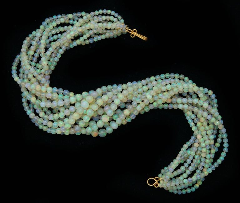A Necklace composed of 12 strands of faceted and graduated opal beads. The beads are attached to an 18kt yellow gold clasp. There are approximately 4,000 cts of opals.  Length:  17.80 inches