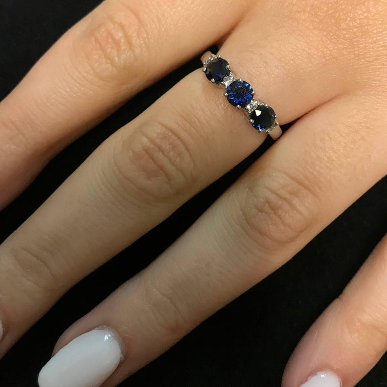 This beautiful band features 3 Blue Sapphires adorned with White Diamonds for a bold and colorful look!  Material: 14k White Gold Gemstones: 3 Round Blue Sapphires at 1.22 carats. Measuring 4.4mm Diamonds: 4 Round White Diamonds at 0.14 Carats.
