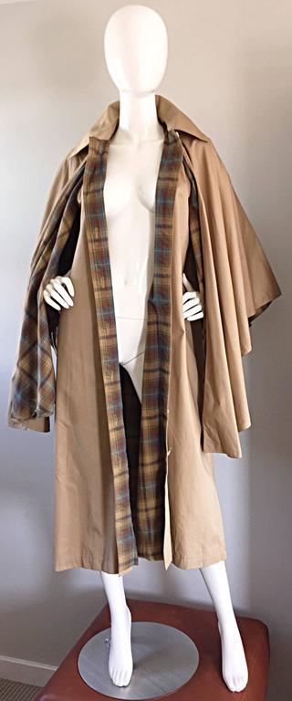 "Absolutely AMAZING Rare vintage Yves Saint Laurent YSL ""Rive Gauche"" dark khaki cape! Trench style, with classic YSL style. Plaid interior (fully lined) that peaks through when worn. Pockets at both sides of waist. Functional horn buttons up the"