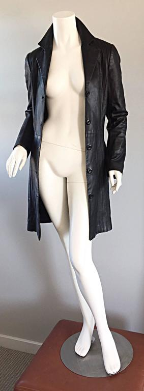 Chic Katayone Adeli early 2000s black leather belted trench jacket! Intricate vertical stitching throughout. Slim fit, that is the perfect everyday jacket! Can even be worn as a dress! Attached belt, with pockets at both sides of the waist.