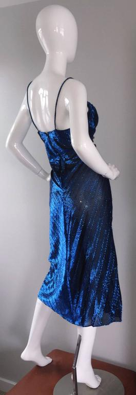 Sexiest vintage Samir 1970s disco dress! Blue metallic color, with intricate pleating throughout the front. Mock buttons down the bodice. Spaghetti straps, with a feminine bust line. Looks great on, and can be worn with, or without stockings.