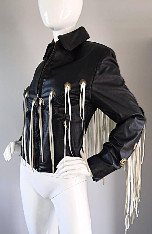 Amazing vintage black leather jacket, with white fringe throughout the front and back! Embellished with brass plates, also on both the front and back. Zips up the bodice. Looks so great on...literally sways with every move, but not in an annoying