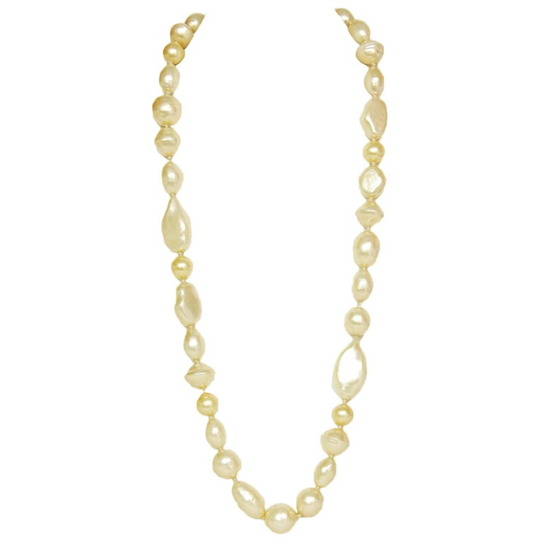 Chanel Vintage '83 Long Pearl Strand Necklace Features different shaped faux pearls with red gripoix closure   Year of Production: 1983 Color: Ivory, goldtone and red Materials: Faux pearls, red gripoix and metal Closure: Hook closure Stamp: Chanel