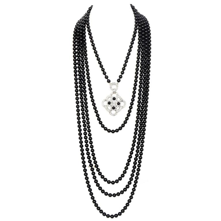 100% Authetic Chanel 2016 Black Beaded Necklace.  Features 5 strands of black glass beads at different lengths complimented by a clear crystal camelia pendant with black bead detail and CC logo.  Made In: Italy Year of Production: 2016 Color: