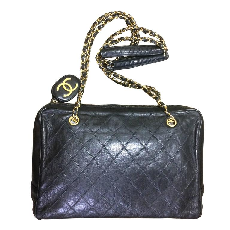 Vintage CHANEL black goatskin shoulder bag with gold tone chains and cc charm. 1