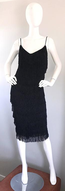 Spectacular 1970s JOY STEVENS black fully fringe sleeveless flapper dress! This statement maker features multiple tiers of fringe throughout the entire front, back and sides of the dress. Comftorable jersey material stretches to fit. Looks