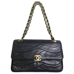 Chanel Vintage black 2.55 shoulder bag with wavy stitches and rope strings.