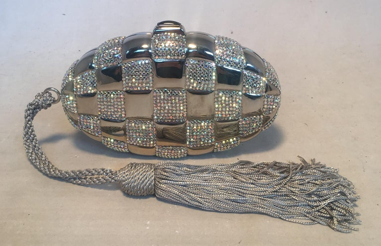 FABULOUS Judith Leiber Swarovski Crystal Checkered Grenade Minaudiere Evening Bag in excellent condition. Silver exterior body with iredecent Swarovski crystals in a checkered pattern throughout. Corded grey nylon rope tasseled handle to wear around