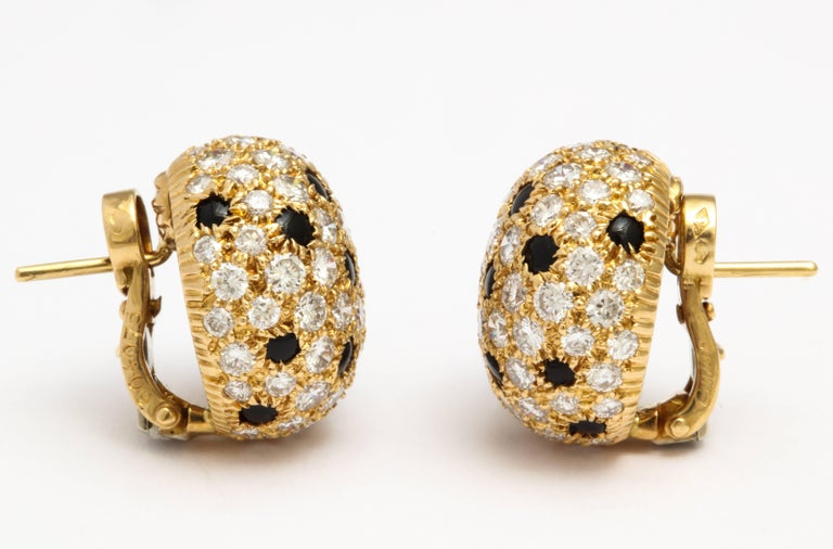 A pair of earrings by Cartier set in 18 karat yellow gold. Each bombé circular cluster has pavé-set brilliant-cut diamonds with a total weight of approximately 6 carats, and is interspersed by buff-top onyx spot detail. French marks.   Signed