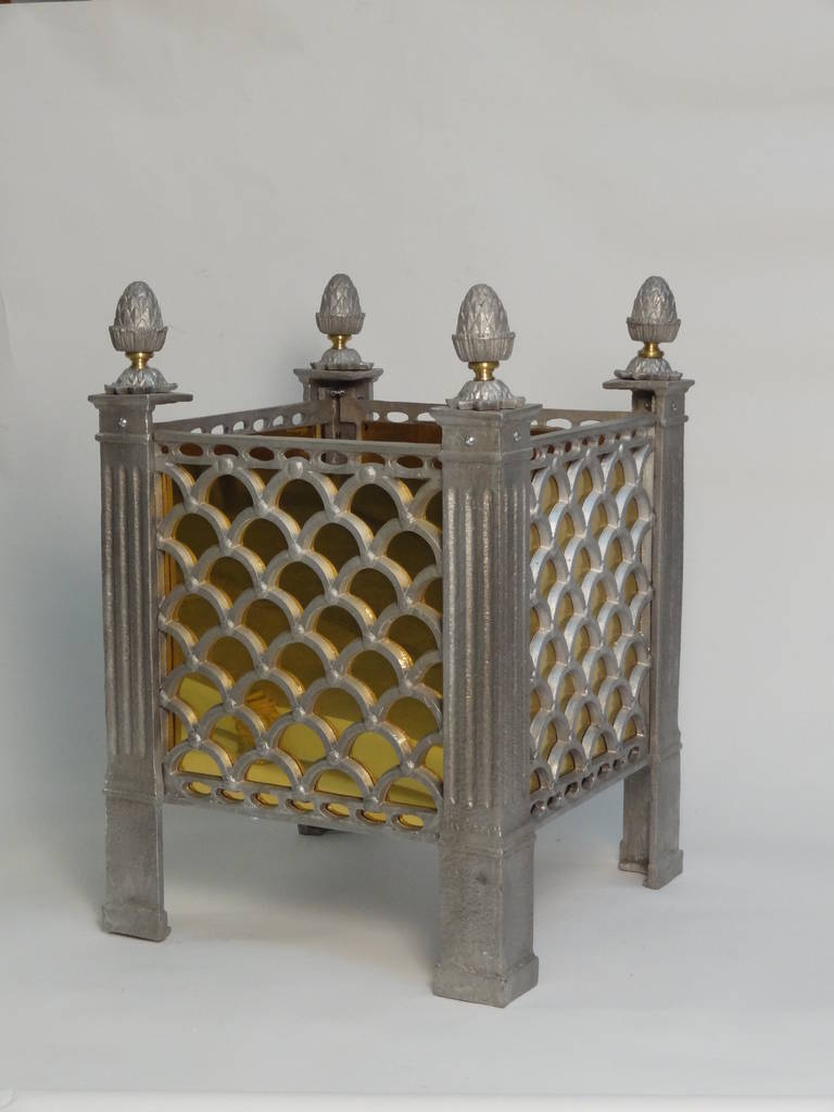 A cast aluminum garden planter with open fan-shaped trellis sides and fluted pilaster legs topped by pine-cone finials with brass details. Shown with brass liners. Also available without liners.