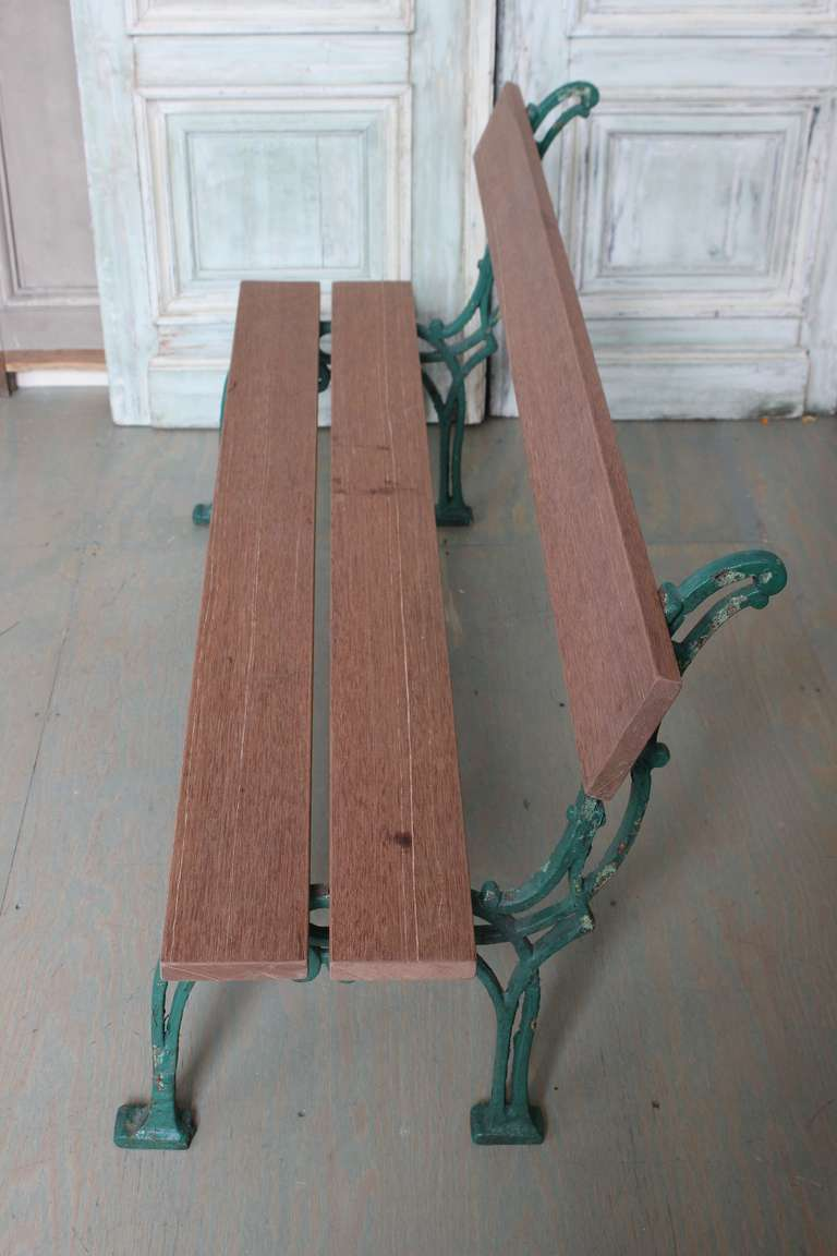 The green cast iron legs are French early 20th century. The solid mahogany seat and back planks are recent. By nature mahogany will weather very nicely, but can be easily painted.  This price of this item has been reduced. This is the final net