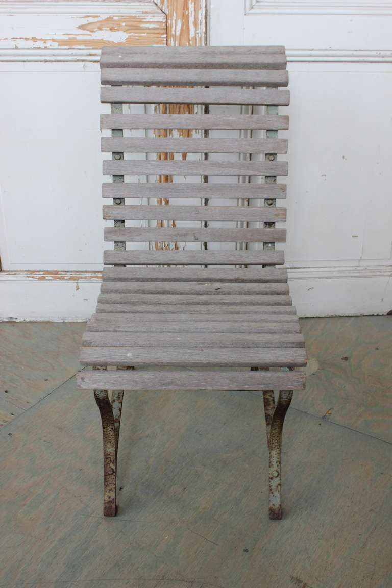 Single chair, faded wooden slats on a rusty, painted iron frame.