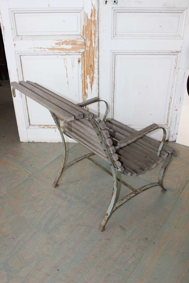 French garden chair, weathered wooden slats on a rusted painted iron frame.