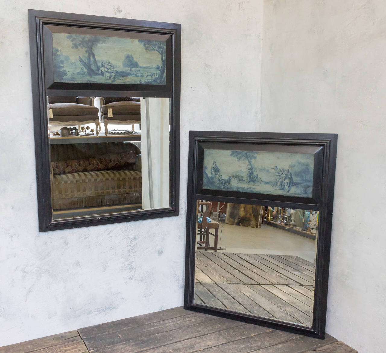 Pair of French 19th century trumeau mirror with ebonized carved wooden frame. There are blue tone paintings of French country life. The mirrors are beveled.