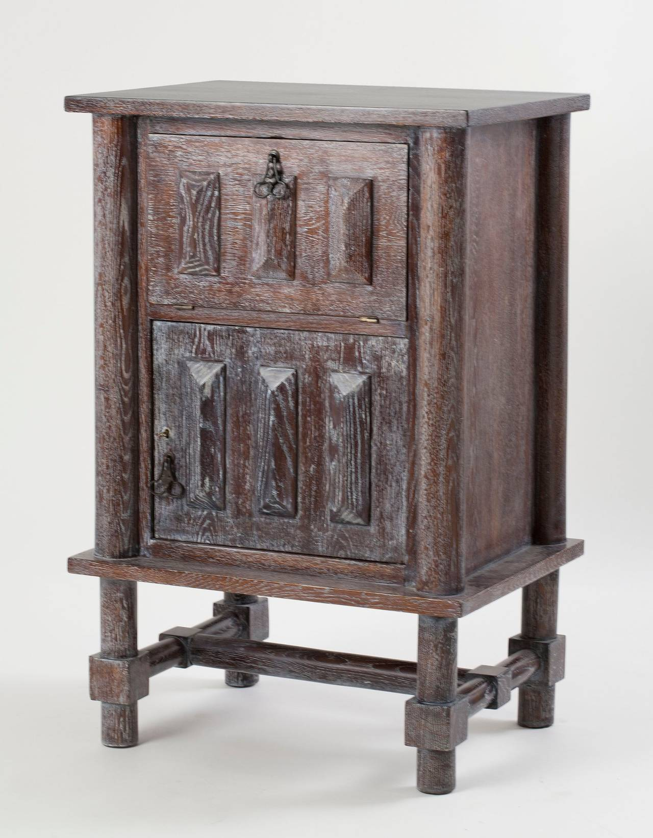 Two-door cabinet in limed oak with wrought iron handles, by Jacques Adnet  For illustrations of similar, larger cabinets, see: Cheronnet, Louis. Jacques Adnet. Paris: Art et Industrie, 1948. pl. 22. Hardy, Alain-René and Gaëlle Millet. Jacques