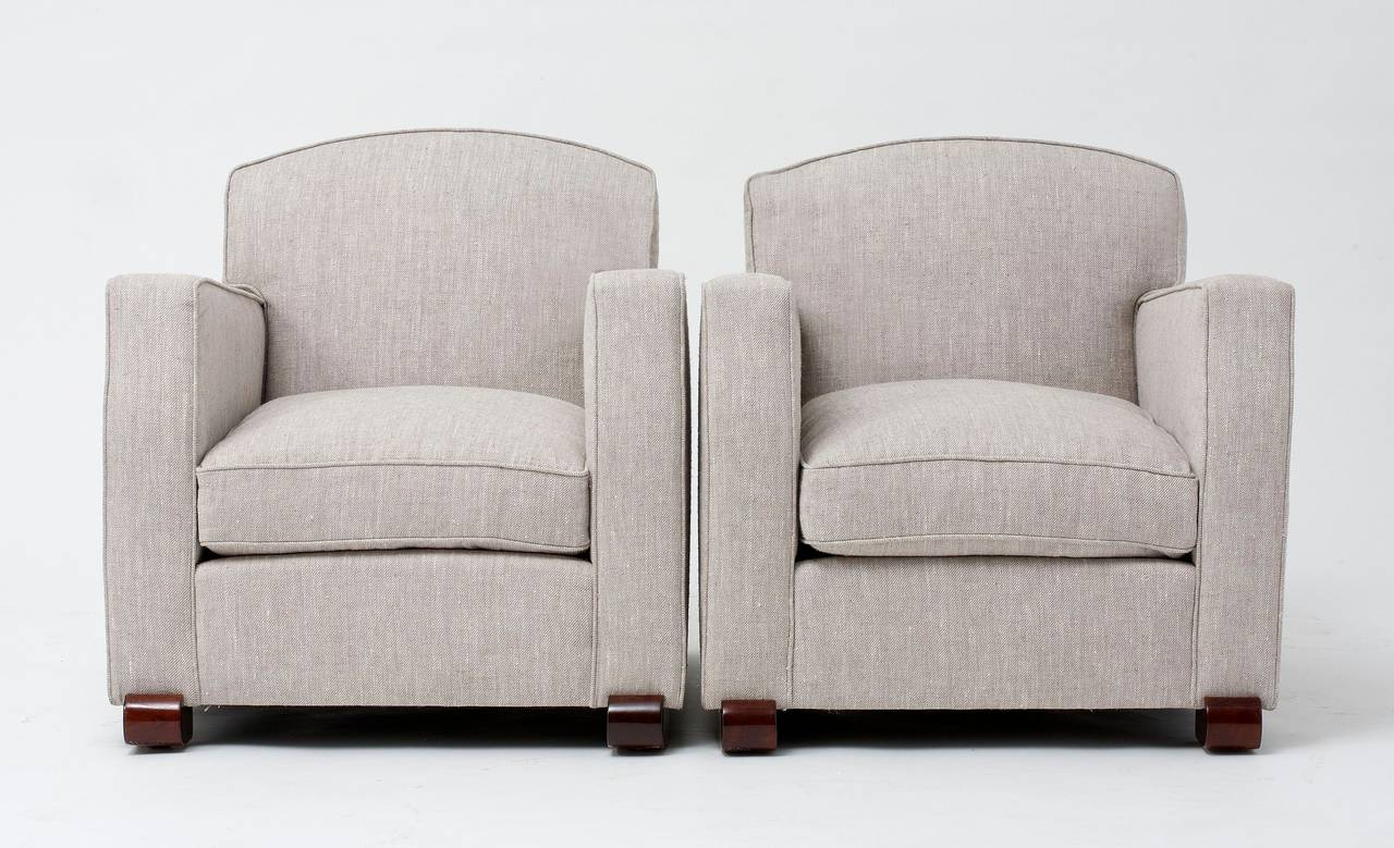 Pair of club chairs by Maison Leleu with walnut feet.