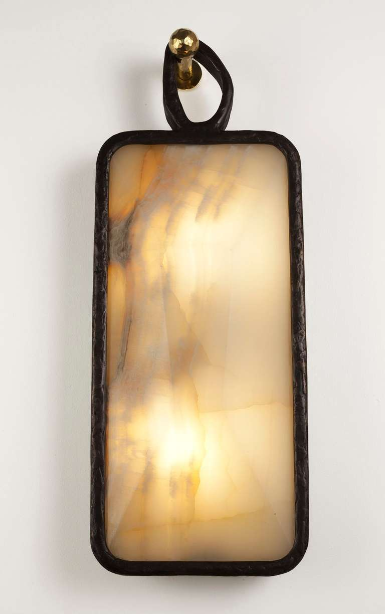 Cast bronze and onyx sconce with a patinated cast bronze hook by Rome based architect Achille Salvagni, recognized worldwide for bringing together Italian craftsmanship and his passion for luxurious materials and traditional techniques.   Edition of