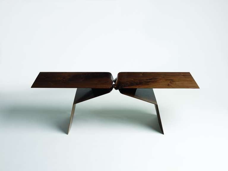 This sculptural hand-carved table is part of a line of contemporary furniture designed by blending digital technology with fine traditional craftsmanship. Carved of walnut, the piece features two crisscrossing buttresses, which, twisting 180 degrees