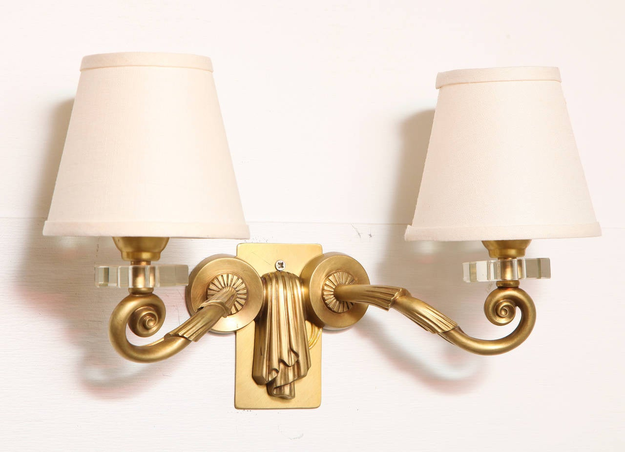 Pair of two-arm gilt bronze sconces by Maison Leleu, with Bohemian crystal bobeches. Gilding by Monin.  For illustrations of this identical model, see: Mobilier et De´coration, no.9. December 1955. 2. Siriex, Franc¸oise. The House of Leleu. New