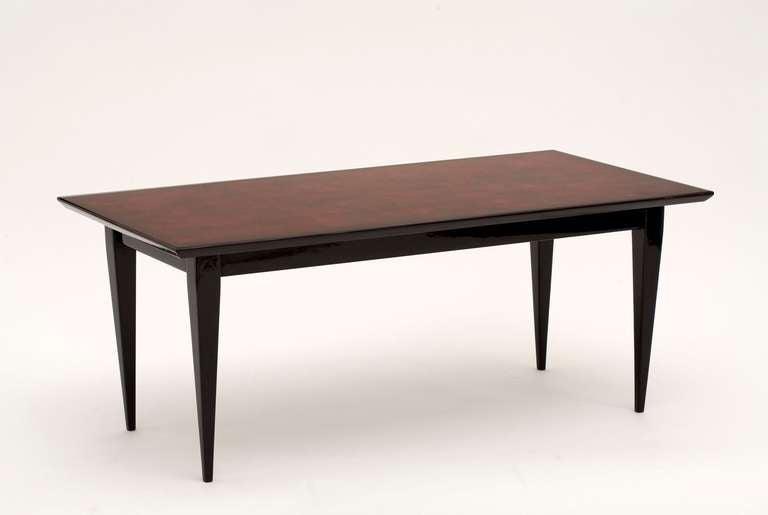 Coffee table by Bernard Dunand with its original lacquered top. The tabletop is a red/brown lacquer and the legs are in black lacquer. 
