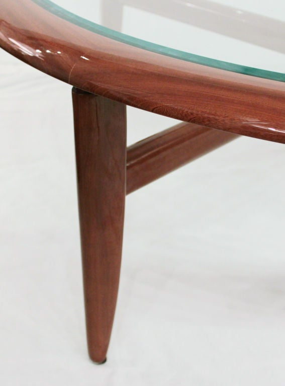 Round coffee table in highly lacquered mahogany with X-base and beveled glass top by Adam Tihany for Pace Collection, Venezia Series, American, 1980s.